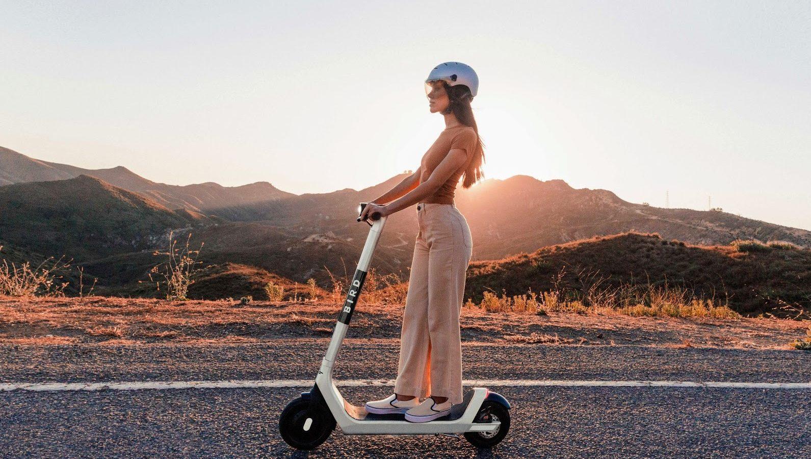 Woman riding Bird scooter